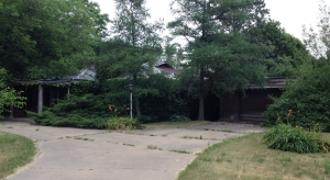 June 30, 2012: A tarp covers the roof and the front of the house is overgrown.